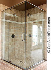 Modern new glass walk in shower with beige tiles and two heads.