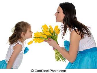 Mom and daughter enjoying the fragrance of flowers.