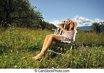 a pretty girl sleeping on a deck chair in the middle of a lawn during a sunny day.