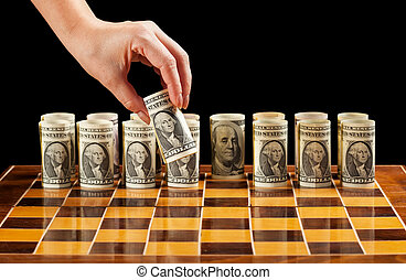 Money strategies concept - dollar bills on chess board manipulated by woman hand