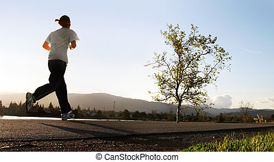 Young woman jogging alond a river in the morning