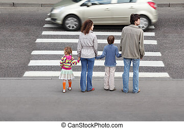 mother and father holds hand of little daughter and son and standing near pedestrian crossing, behind, car on road