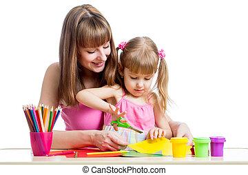Mother teaches preschooler kid to do craft items. DIY concept.