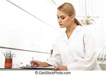 Odontologist filling up a form in office