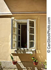 opened window with flowerpots