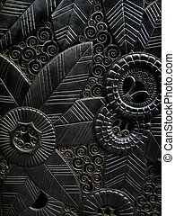 Closeup of an ornately carved metal door