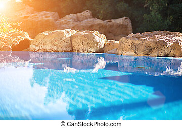 Outdoor inground residential swimming pool in backyard with hot tub. Sun flare