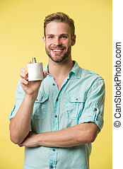 Overpowering mens scent. Happy guy hold perfume bottle yellow background. Advertising perfume. Eau de toilette. Cosmetic product. Cosmetics. Perfume and cologne. Shop fragrance perfume, copy space