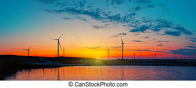 Panorama of wind farm by the sea at sunrise