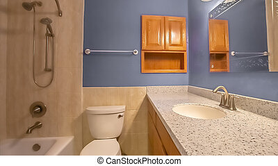 Panorama Small bathroom interior with vanity area adjacent to the toilet and bathtub