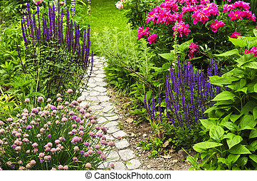 Lush blooming summer garden with paved path
