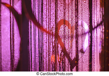 Photo of the heart on the misted window with light highlights.