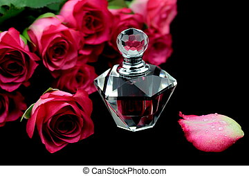 Pink roses and perfume glass bottle on black background