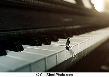 A woman sitting on a key of a piano alone