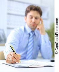 Portrait of a business man filling a form, focus on hand holding the pen