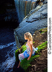 Portrait of beautiful girl enjoying beauty of nature on brink of precipice of river waterfalls in early summer morning