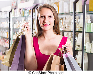 woman displaying shopping bags with purchase in the natural cosmetics shop