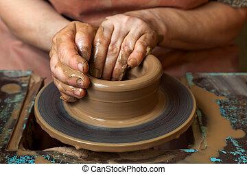 Potter creates a pitcher on a pottery wheel