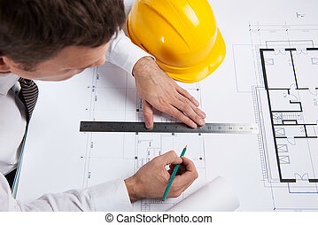 professional architect drawing construction plan. man sitting at table with pencil and ruler