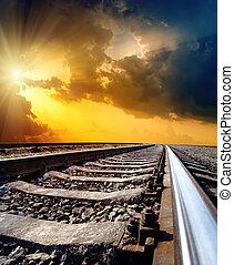 railway to horizon under dramatic sky with sun