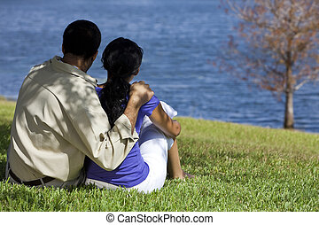 Rear view of African American man and woman couple sitting by a blue lake with a single tree. Concept shot for love, romance or loss.