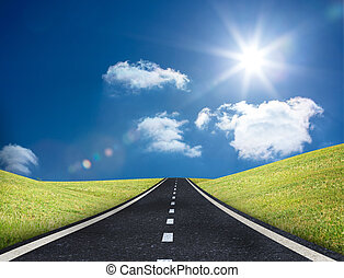 Road leading out to the horizon in the middle of a sunny field