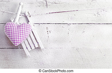 Romantic checked violet needlework heart for Valentines hanging on old painted white boards with copyspace