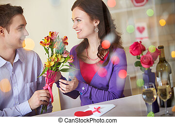 A young man giving floral bouquet to pretty girlfriend