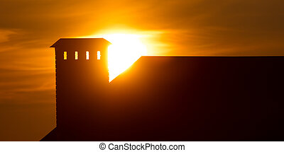 Roof of the house at sunset