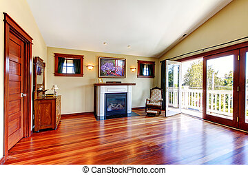 Room with beautiful chery hardwood floor and fireplace with open doors to the balcony.