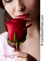 Close-up of attractive woman holding red rose and enjoying its smell