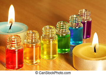Row of six bottles with colored aroma oils and two candles on table