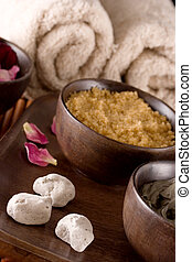 Spa accessories: scented stones, body scrub with brown sugar crystals, mud, towels