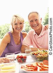 Senior couple eating outdoors