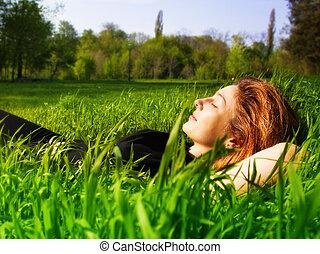 Serene woman relaxing outdoor in fresh grass