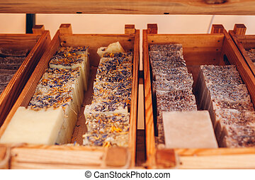 Showcase with hand-made soap in wooden boxes. Sale of organic cosmetics in store. Lavender fragrance