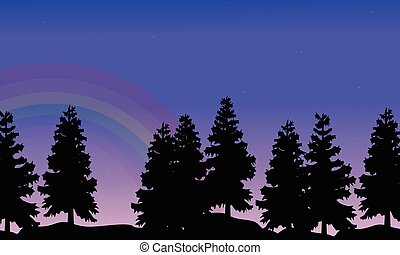 Silhouette of tree lined with rainbow landscape