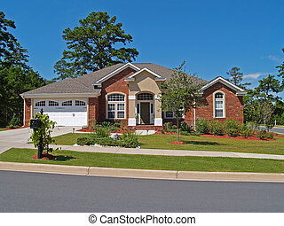 Single story brick residential home with the garage in the front.