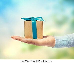 Small blue ribbon gift box on a hand