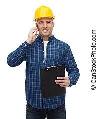 smiling builder in helmet calling on smartphone