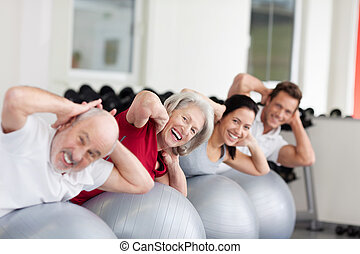 Smiling elderly woman training in a group