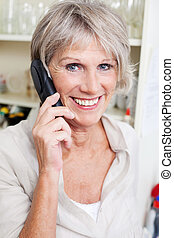 Smiling attractive grey haired senior lady talking on a telephone in her house
