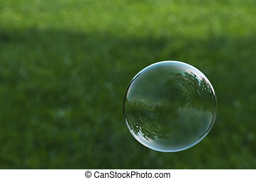 Soap bubble flying in front of grass