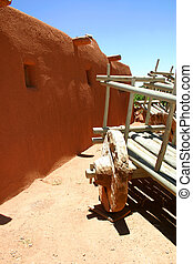 Antique wooden wagon sitting in front of adobe structure in the desert southwest of the United States.