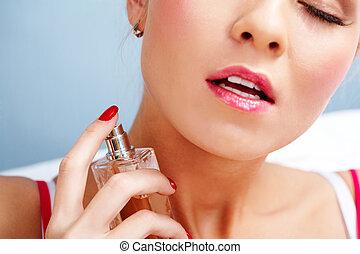 Photo of sensual woman spraying perfume onto her neck skin