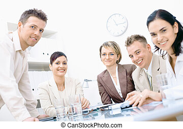 Five business colleagues sitting around table and working together, looking at camera, smiling.