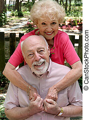 A happy senior couple embracing outdoors. They are still in love after many years together.