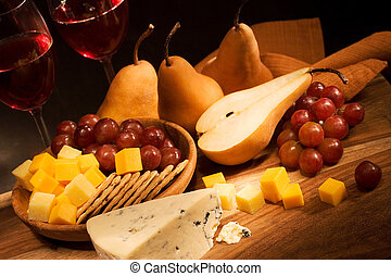 Still life with cheese, fruits and wine in warm light.