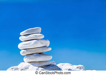Stones balance, hierarchy stack over blue sea in Croatia. Spa or well-being, freedom and stability concept on rocks.