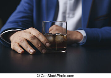 Stressed asian businessman holding a glass of whiskey he sleeping and Data Charts, business document at office desk. alcohol addiction - drunk businessman concept